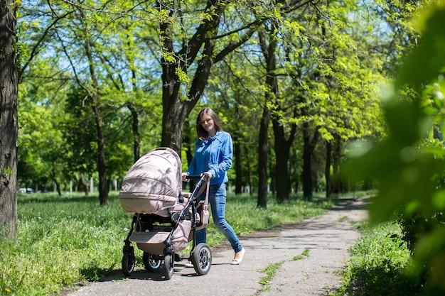 Jeune mère marchant et poussant une poussette dans le parc