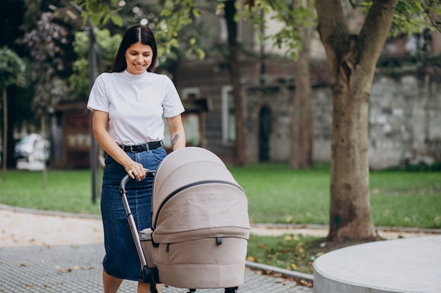 Jeune mère marchant avec poussette de bébé dans le parc