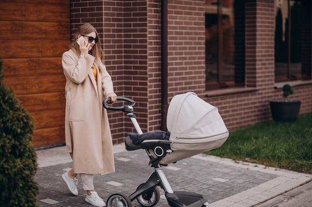 Jeune mère marchant avec poussette bébé