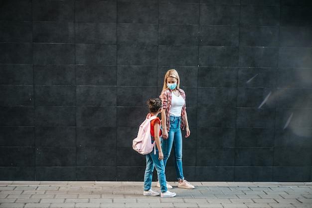Jeune mère marchant avec sa petite fille dans la rue de la ville. ils portent des masques de protection du visage. retour à l'école et nouveau concept de mode de vie du coronavirus.