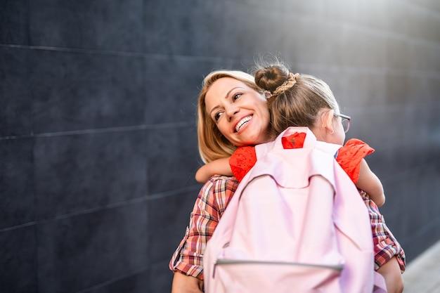 Jeune mère marchant avec sa petite fille à l'école primaire. retour au concept de l'école.