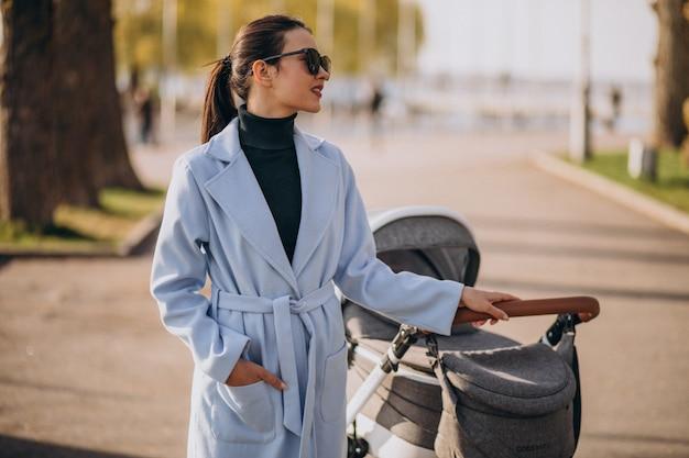 Jeune, mère, marche, voiture bébé, dans parc