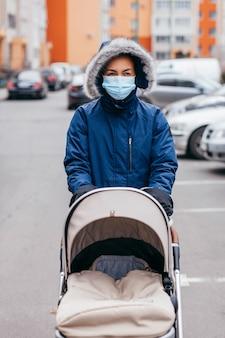 Jeune mère en masque chirurgical et gants marchant avec bébé en plein air en europe
