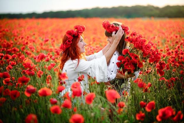 La Jeune Mère Met Une Couronne De Fleurs De Pavot Sur La Tête De Sa Fille En Gros Plan Photo Premium