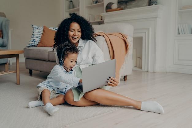 Jeune mère métisse positive et fils garçon mignon ayant un appel vidéo sur un ordinateur portable