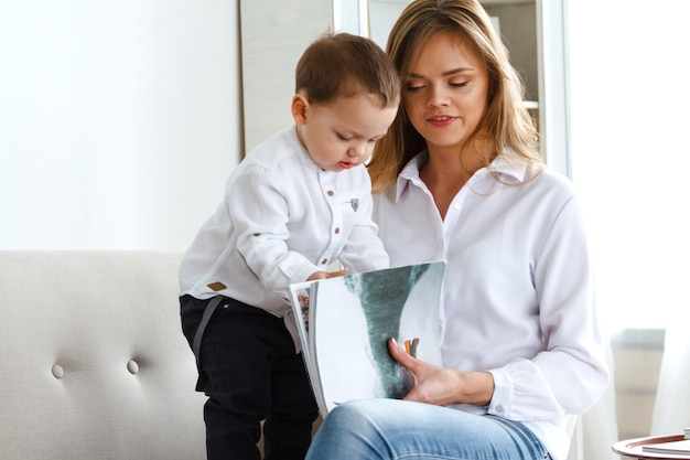 Une jeune mère avec un mignon petit fils lisant un magazine dans un salon confortable et lumineux
