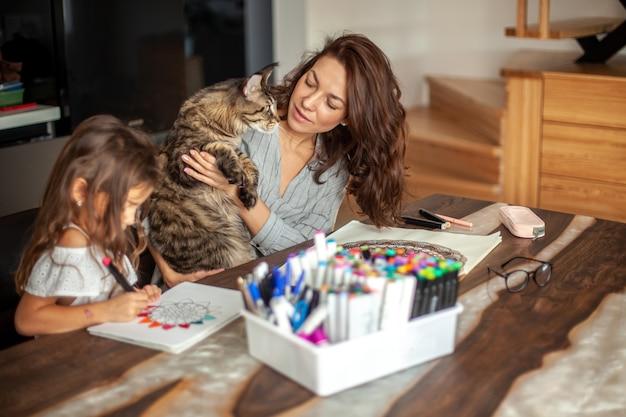 Une jeune mère mince et belle avec une fille mignonne et un chat maine coon peint dans la cuisine...