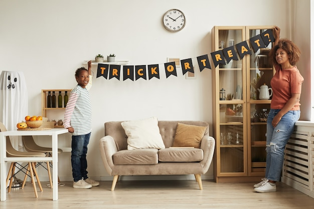 Jeune mère moderne et son fils suspendu guirlande avec lettrage trick or treat sur le mur pour la fête d'halloween