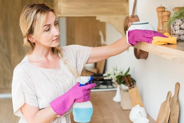 Jeune mère nettoyant les étagères de la maison