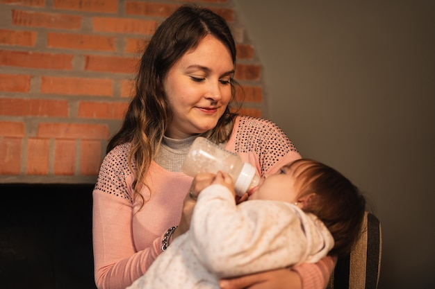Jeune mère nourrissant sa mignonne petite fille avec une bouteille de lait maternisé.