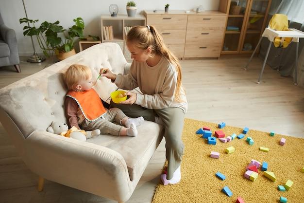 Jeune mère nourrit son bébé sur le canapé dans le salon