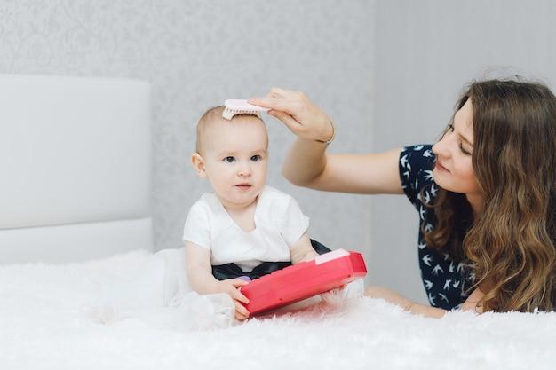 Jeune mère peignant sa fille