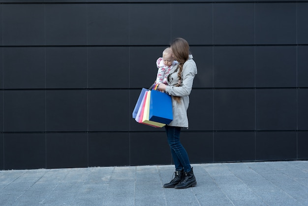 Jeune, mère, petite fille, bras, achats, sacs, main