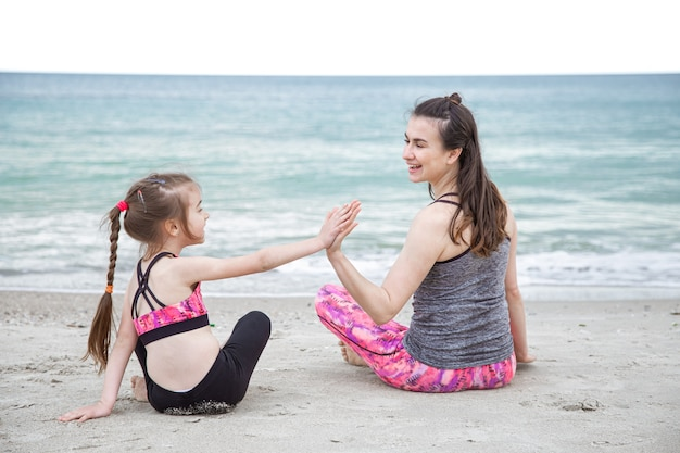 Jeune mère avec une petite fille en tenue de sport sont assis sur la plage dans le contexte de la mer. des valeurs familiales et un mode de vie sain.