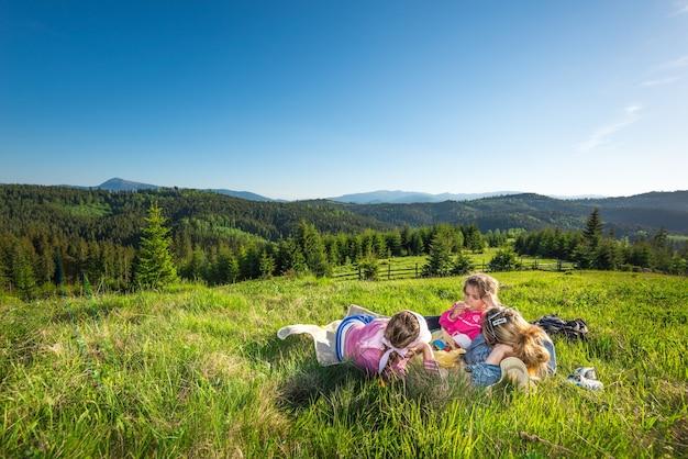 Jeune mère et petites filles s'allongent sur une pente envahie par l'herbe ou admirer la vue magnifique sur un renard poussant sur les collines