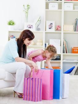 Jeune mère avec peu de curiosité fille ouverture achat après avoir fait du shopping à la maison