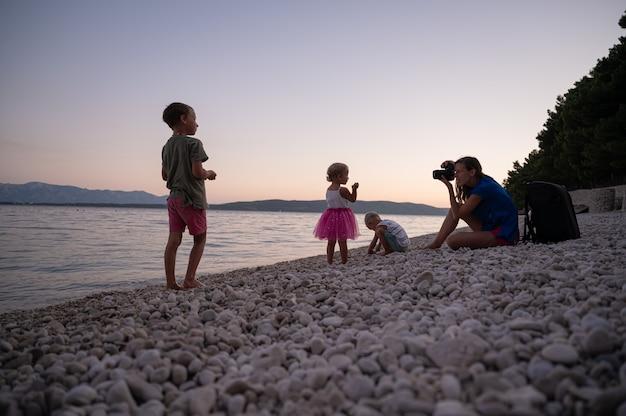 Jeune mère photographiant ses trois enfants jouant sur une plage de galets par une belle soirée d'été.