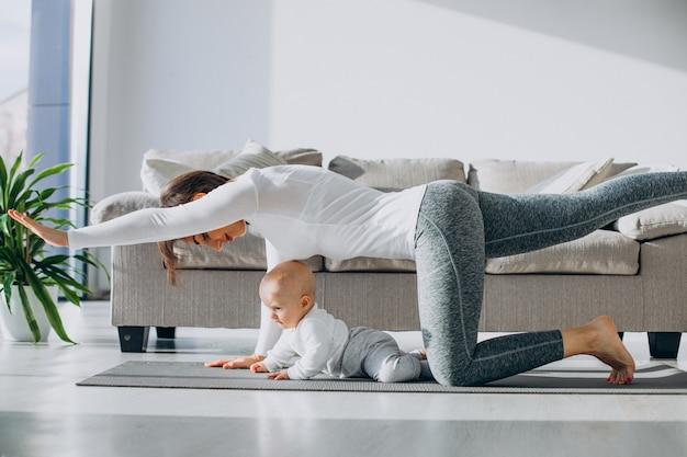 Jeune mère pratique le yoga avec son petit garçon sur un tapis