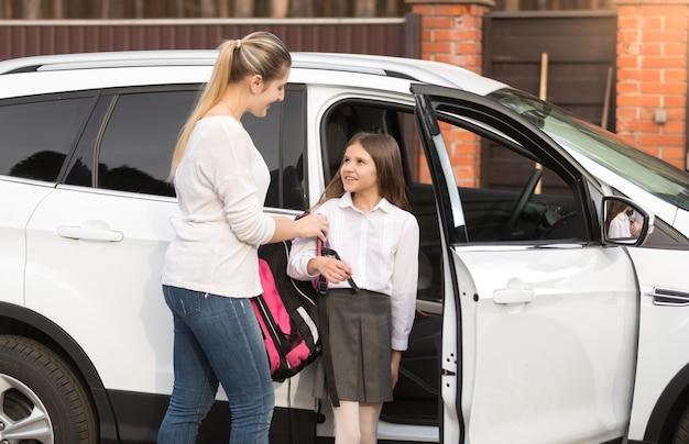 Jeune mère prenant sa fille à la maison de l'école en voiture