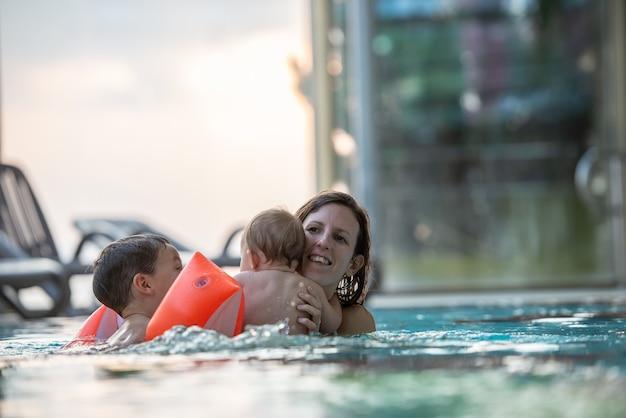 Jeune mère profitant d'un moment de complicité avec ses deux enfants dans une piscine.
