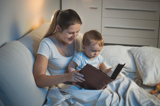 Jeune mère racontant des histoires à son adorable petit garçon au lit