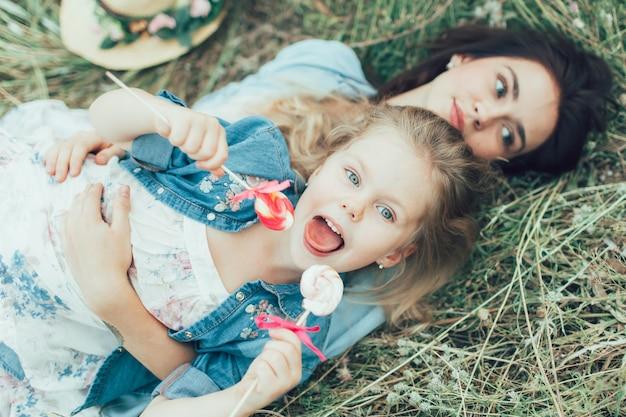 La jeune mère et sa fille sur l'espace d'herbe verte