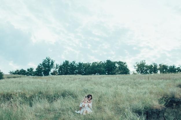 La jeune mère et sa fille sur l'herbe verte