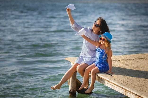 Jeune mère et sa jolie fille au bord de la mer, le lancement d'avions en papier dans l'air et de rire