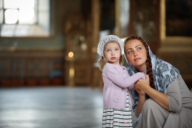 Jeune mère et sa petite fille blonde de race blanche avec des bougies dans l'église russe orthodoxe