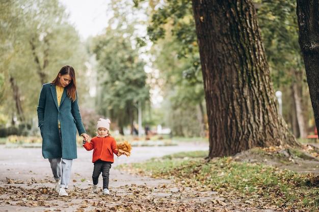Jeune mère avec sa petite fille dans un parc d'automne