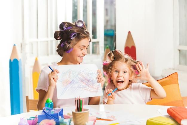 La jeune mère et sa petite fille dessinant avec des crayons à la maison
