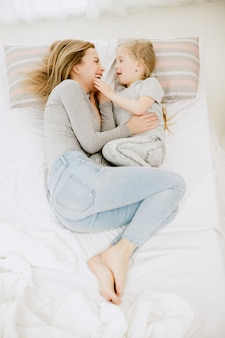 Jeune mère et sa petite fille à la maison au matin ensoleillé