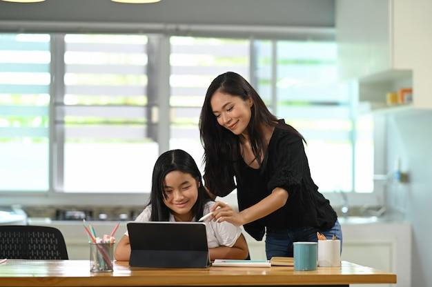 Une jeune mère se lève et donne des cours particuliers à sa fille au bureau des élèves en bois par tablette informatique.