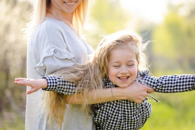 Une jeune mère secoue sa petite fille dans ses bras dans le parc du printemps. la fille écarta les bras et vola comme un avion dans les bras de sa mère. maman mignonne avec sa fille s'amuse dans le parc printanier.