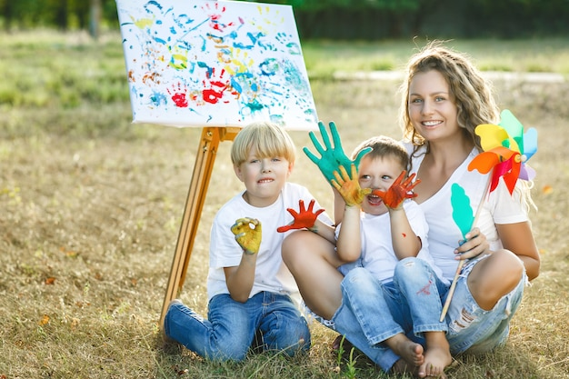 Jeune mère séduisante s'amusant avec ses enfants dans le parc. enthousiaste famille s'amusant en plein air. maman joue avec ses enfants.
