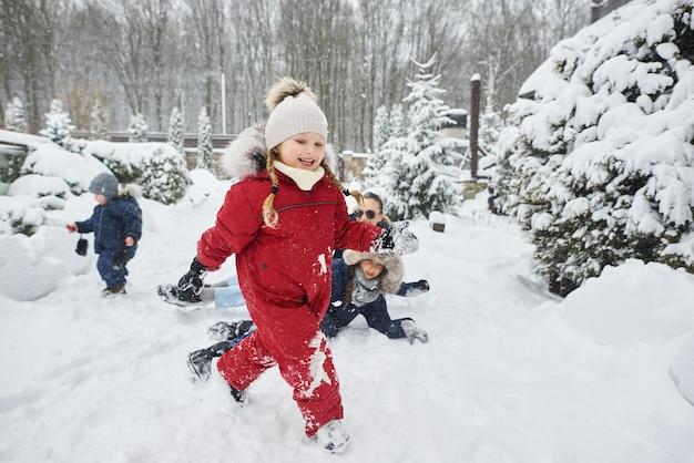 Une jeune mère avec ses enfants s'amusant en hiver