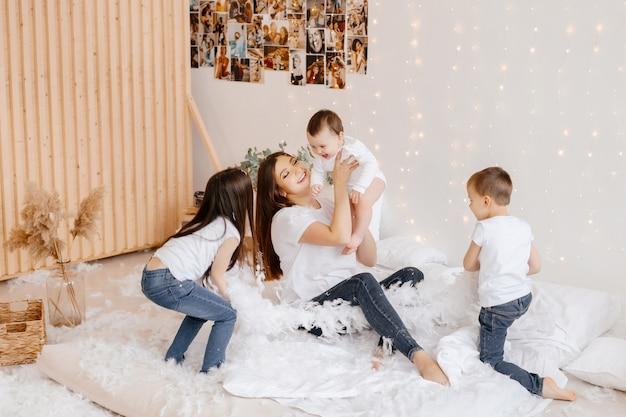 Jeune mère et ses trois enfants en jeans et t-shirts jouent en s'amusant assis sur le sol