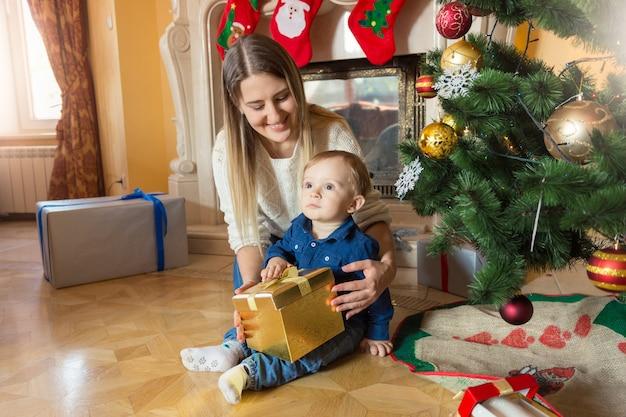 Jeune mère avec son bébé assis à l'arbre de noël et regardant à l'intérieur de la boîte-cadeau