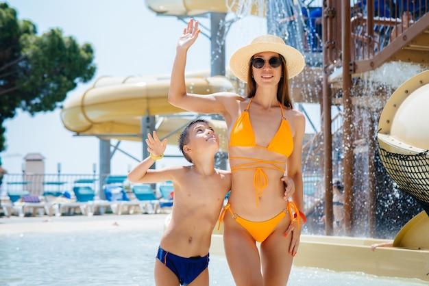 Une jeune mère et son fils sourient joyeusement dans le contexte d'un parc aquatique plus grand et moderne par une journée ensoleillée. bonnes vacances vacances. vacances d'été et tourisme.
