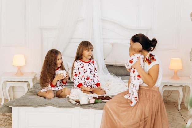 Jeune mère avec son petit bébé est assise sur le lit avec ses deux filles en pyjama mangeant des biscuits au cacao avec des guimauves .