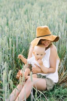 Une jeune mère et son petit enfant assis près du blé