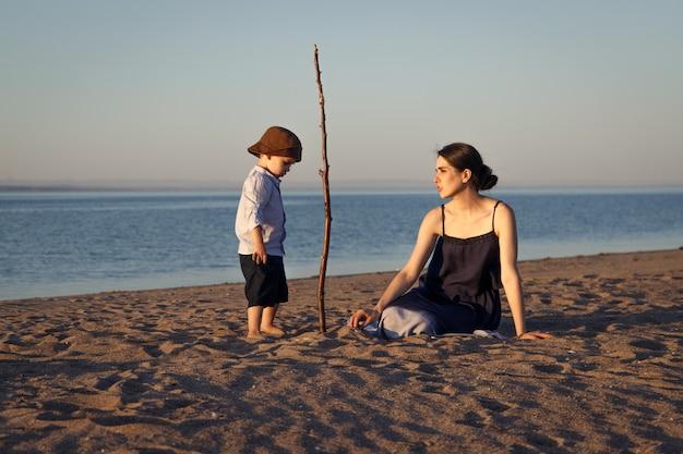 Jeune mère avec son petit fils de 3 ans passe du temps sur la plage à jouer à différents jeux.