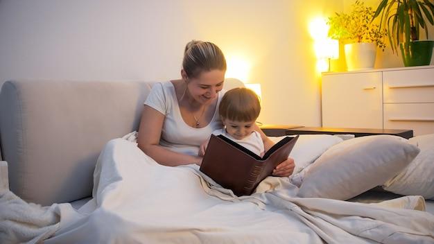 Jeune mère souriante avec un petit garçon lisant un livre au lit.