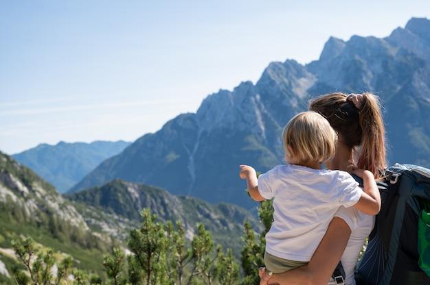 Jeune mère tenant sa petite fille regardant une belle vue sur les montagnes alors qu'elles marchent ensemble par une journée ensoleillée.