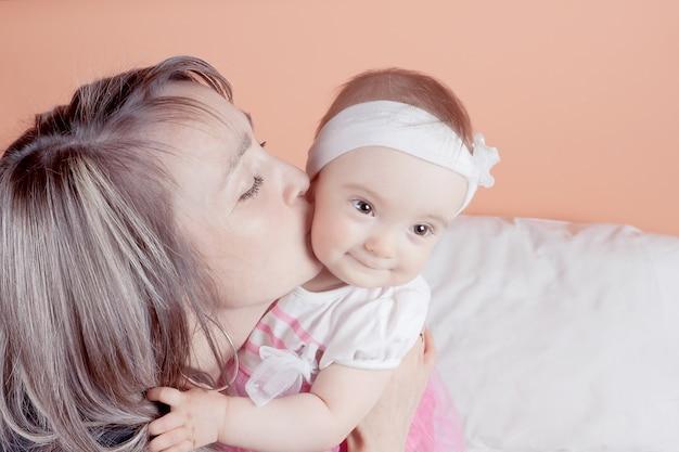 Une Jeune Mère Tenant Son Bébé L'embrasse. Fermer. Photo Premium