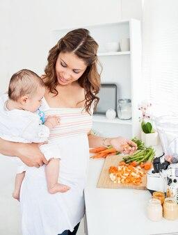 Jeune mère tenant son bébé tout en préparant la carotte pour le déjeuner