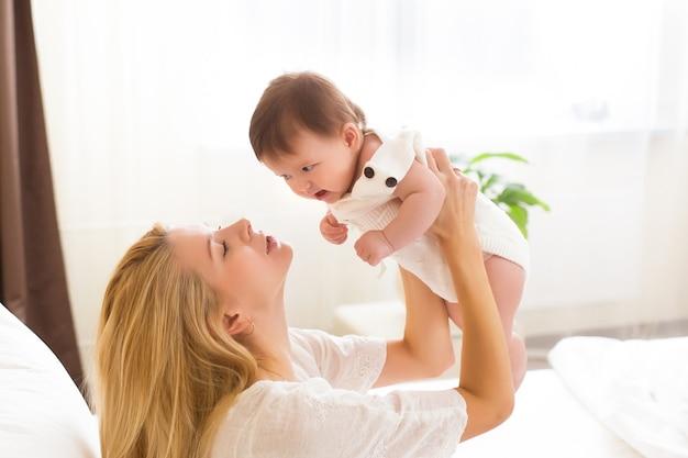 Jeune mère tenant son enfant nouveau-né. bonne maman allaite bébé. femme et fille nouveau-née ensemble dans une chambre blanche à la maison. mère allaitant bébé. mode de vie familial