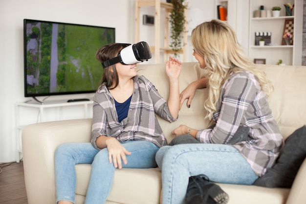 Jeune mère utilisant des gadgets modernes pour l'éducation de sa petite fille. lunettes de réalité virtuelle.