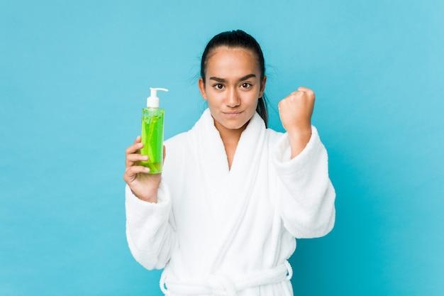 Jeune métis indien tenant une bouteille d'aloe vera montrant une expression faciale agressive.