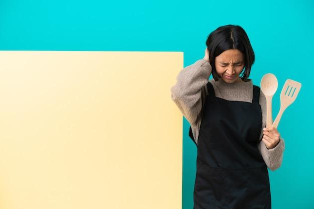 Jeune métisse cuisinier femme avec une grande pancarte isolée sur fond bleu frustré et couvrant les oreilles